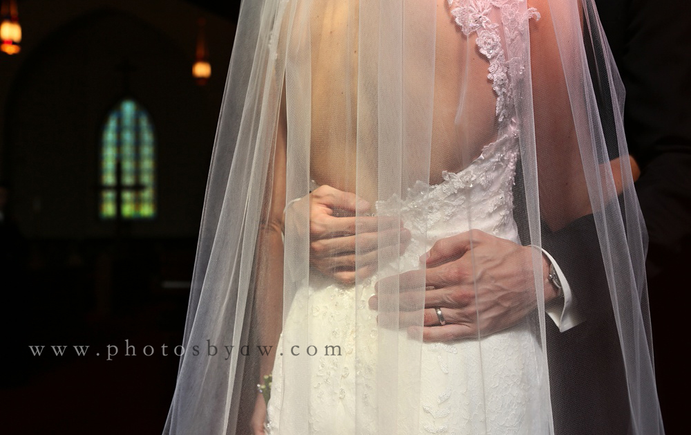 grooms_hands_on_brides_back_veil